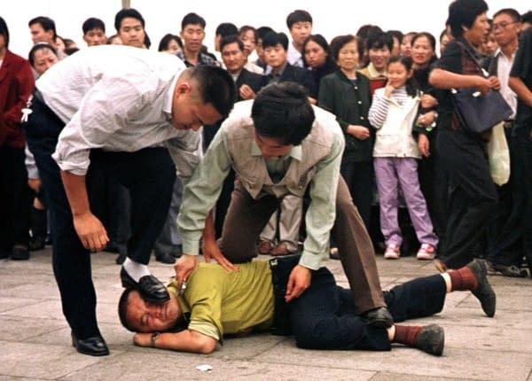praticanti Falun Gong pestati polizia borghese
