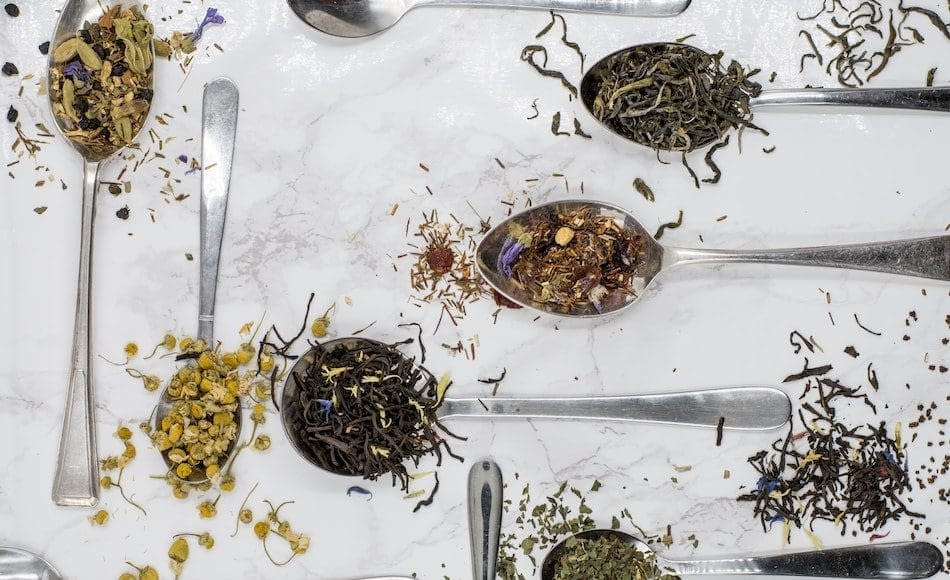 sei cucchiai d'argento con foglie essicate di tè posati su una tovaglia bianca