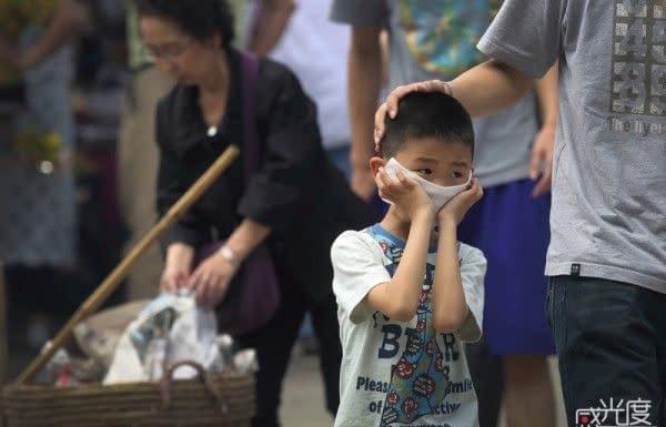 Ragazzo si protegge il viso dal fumo al festival di Qingming.