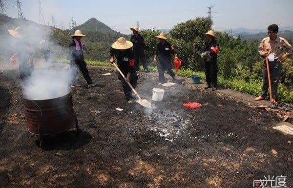 Gli addetti alle pulizie puliscono dopo che è scoppiato un incendio nell'erba.